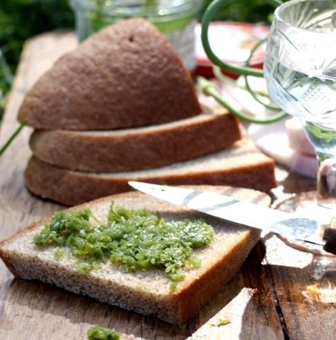 Чёрный хлеб с пастой из чесночных стрелок и рюмка с прозрачной жидкостью на столе