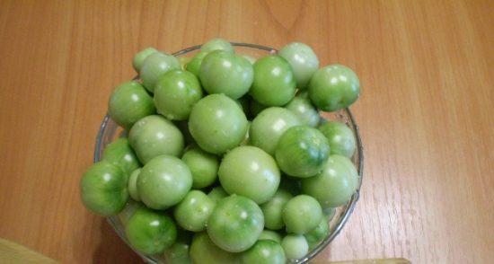 Небольшие зелёные помидоры в стеклянной ёмкости на деревянном столе