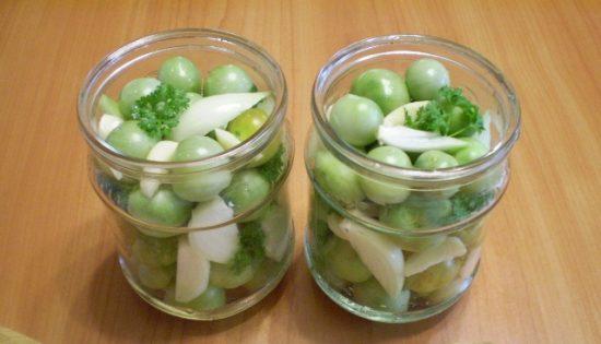 Зелёные помидоры с кусочками репчатого лука, чеснока и веточками зелени в небольших стеклянных банках