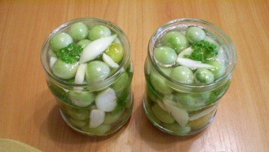 Стеклянные банки с зелёными помидорами и жидкостью