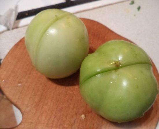 Надрезанные зелёные помидоры на деревянной разделочной доске