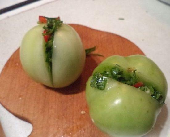 Зелёные помидоры с начинкой из зелени и острого перца на деревянной разделочной доске