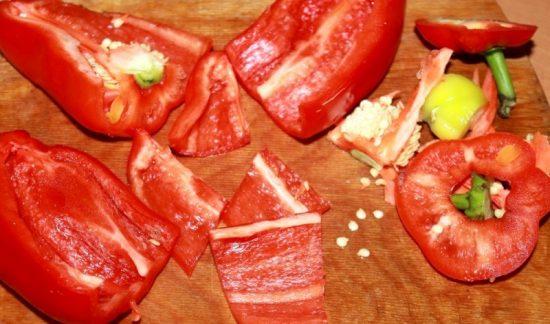 Очищенный от семян и плодоножек красный сладкий перец на деревянной разделочной доске