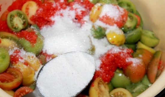 Половинки мелких помидоров разного цвета в кастрюле с сахаром и солью