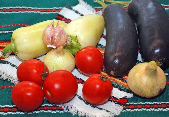 Свежие овощи для лечо из баклажанов на столе с вышитой скатертью и салфеткой