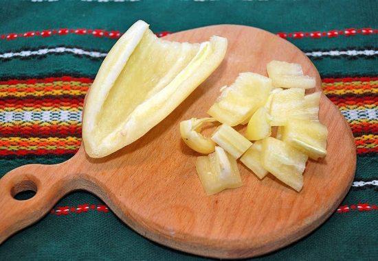 Нарезанный кусочками сладкий перец на деревянной разделочной доске