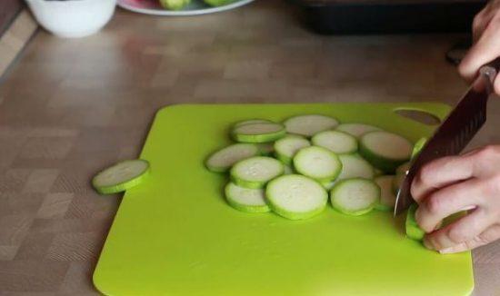 Нарезка кабачков тонкими кружками на зелёной разделочной доске