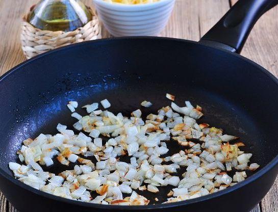 Мелко нарезанный репчатый лук в большой сковороде