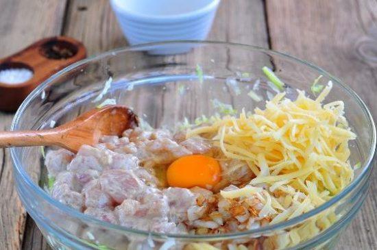 Подготовленные ингредиенты для запеканки с кабачками в стеклянной миске на деревянном столе