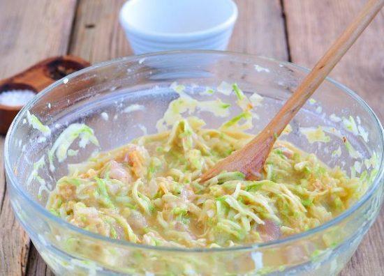 Масса из тёртых кабачков, мяса и других ингредиентов в стеклянной миске на деревянном столе