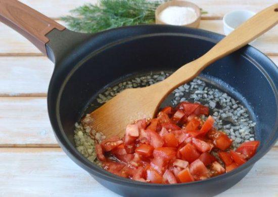 Обжаренный репчатый лук и нарезанные кубиками помидоры в сковороде с растительным маслом