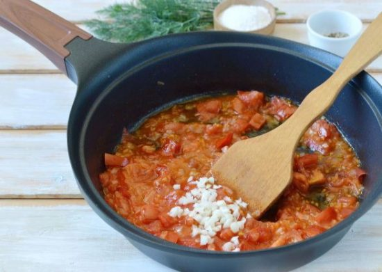 овощная зажарка и рубленый чеснок в большой сковороде с деревянной лопаткой